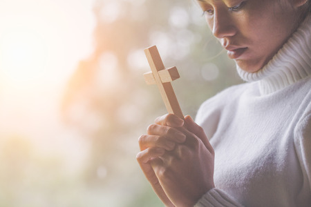 Women pray to God with  the cross of the morning. Woman Pray for god blessing to wishing have a better life. Christian life crisis prayer to god. Stock Photo