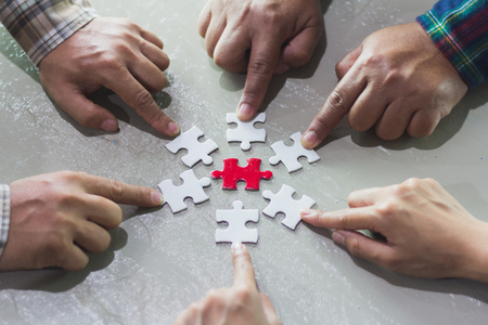 Hands of diverse people assembling jigsaw puzzle, Youth team put pieces together searching for right match, help support in teamwork to find common solution concept, top close up view