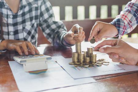 ็Human hand put coins to stack of coins, a saving money for future investment and savings concept. Stock Photo
