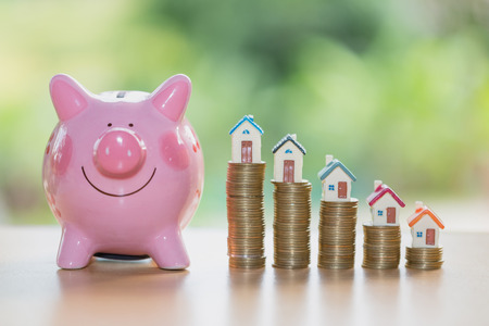 Real estate sale, home savings, piggy bank, coins and a house, loans market concept. Housing industry mortgage plan and residential tax saving strategy. Archivio Fotografico