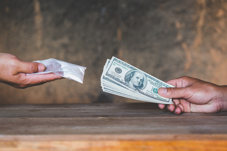 Hand of addict man with money buying dose of cocaine or heroine, close up of addict buying dose from drug dealer, drug trafficking, crime, addiction and sale concept, Stock Photo
