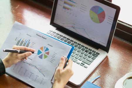 gros plan sur la main d'une femme d'affaires travaillant sur un ordinateur portable avec des informations de graphique d'entreprise financière, analysant les graphiques d'investissement.