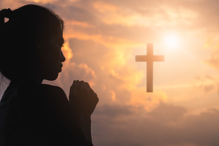 Silhouette of young woman praying with a  cross at sunrise, Christian Religion concept background. Banco de Imagens - 112440294