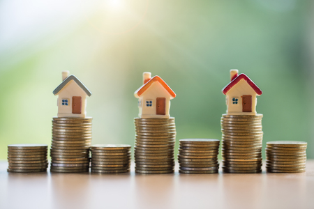 Mini house on stack of coins,Money and house,  Mortgage, Savings money for buy house and loan to business investment for real estate concept. Invesment and Risk Management. Stock Photo