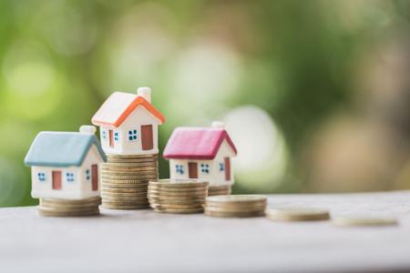 Minihuis op stapel munten, geld en huis, hypotheek, spaargeld voor het kopen van een huis en lening aan bedrijfsinvesteringen voor onroerend goedconcept. Beleggings- en risicobeheer. Stockfoto