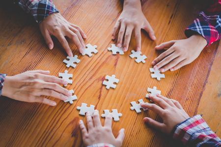 Hände verschiedener Leute, die Puzzles zusammensetzen, Jugendteam setzt Teile zusammen, um nach dem richtigen Spiel zu suchen, Unterstützung bei der Teamarbeit, um ein gemeinsames Lösungskonzept zu finden, Nahaufnahme von oben Standard-Bild