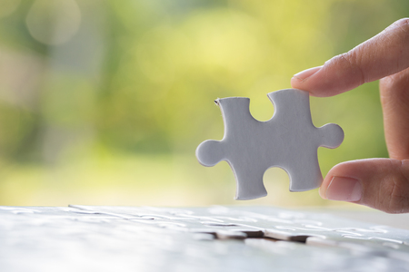 Hand put the last piece of jigsaw puzzle to complete the mission Banque d'images