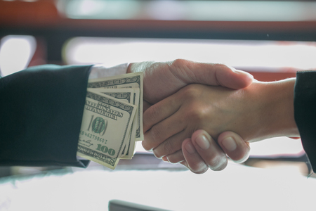 Corrupted businessman sealing the deal with a handshake and receiving a bribe money, anti bribery and corruption concepts Stock Photo