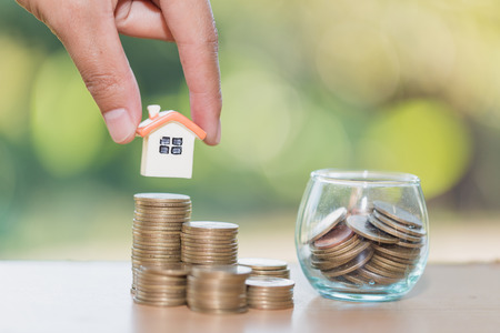 Woman hand hold a  home model put on the stack coin with growing, Savings money for buy house and loan to business investment for real estate concept. Invesment and Risk Management. Archivio Fotografico