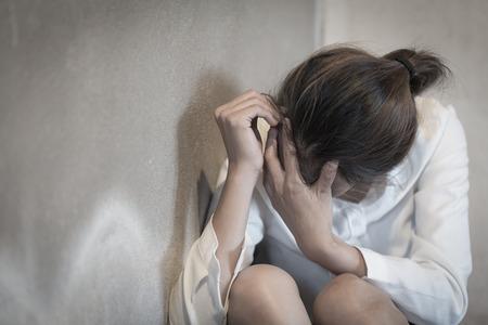 Donna sdraiata sul pavimento che piange di depressione, donna depressa seduta a terra, problemi familiari, cucina, abuso, violenza domestica, concetto di depressione e suicidio.