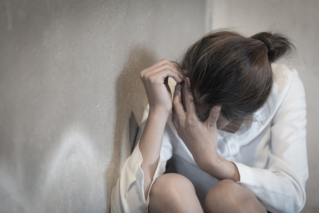 Kobieta leży na podłodze płacze z depresją, Depresji kobieta siedzi na ziemi, problemy rodzinne, kuchnia, nadużycia, przemoc domowa, pojęcie depresji i samobójstwa.