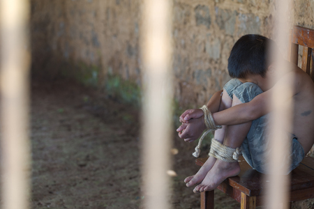 Victim boy with hands tied up with rope in emotional stress and pain, kidnapped, abused, hostage, afraid, restricted, trapped, pitiable, struggle, Stop violence against children and trafficking Concept. Stock Photo
