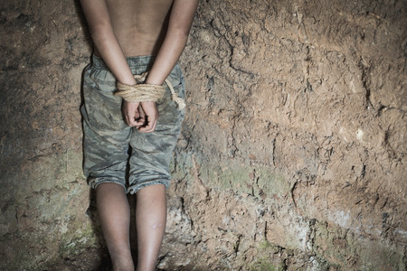 The boy was tied at the corner of the abandoned house, Stop violence against children and trafficking.