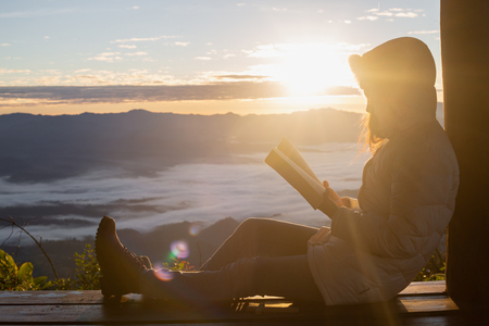 Woman holding reading Bible on Mountain in the Morning- Image