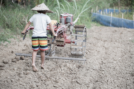 Child labor, Poor children driving a plow farming area, Children have to work because of poverty, World Day Against Child Labour concept. Foto de archivo