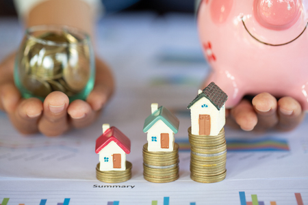 Mini house on stack of coins,Money and house,  Mortgage, Savings money for buy house and loan to business investment for real estate concept. Invesment and Risk Management, hourglass.