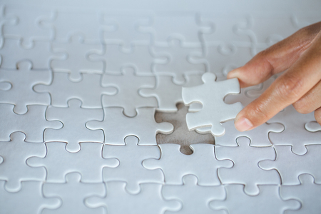 Hand put the last piece of jigsaw puzzle to complete the mission, Business solutions, success and strategy concept