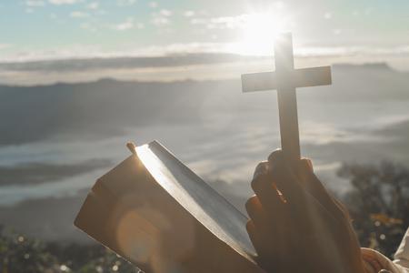 Christelijke vrouw die op de berg bidt met ochtendzonsopgang. Handen gekruist en Heilige Bijbel. Achtergrond