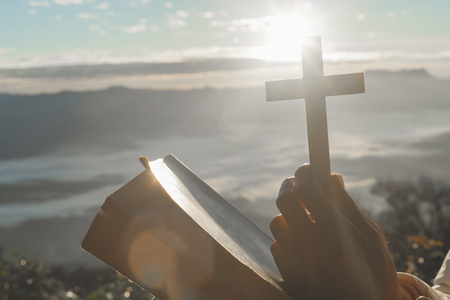 Christian woman praying on the mountain with morning sunrise. Hands crossed and Holy Bible . Background