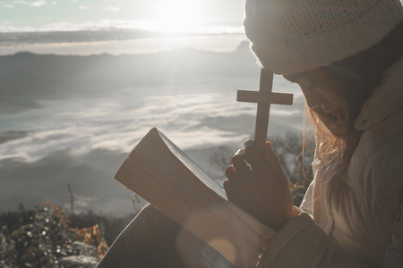 Women pray to God with the Bible and the cross on the mountain background with morning sunrise. Woman Pray for god blessing to wishing have a better life. Christian life crisis prayer to god.
