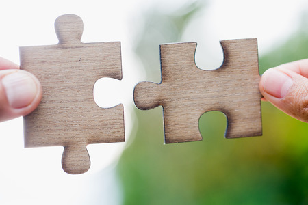Closeup hand of connecting jigsaw puzzle to complete the mission with sunlight effect, Business solutions, success and strategy concept