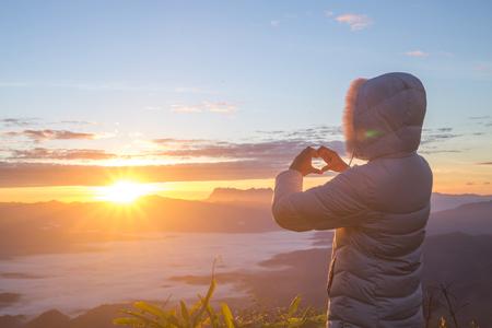 Vrouw die hartvorm maakt tijdens zonsopgang, God is liefdesconcept, hartvorm, bergtoerisme, symbool van liefde, de manifestatie van liefde, uitdrukking van gevoelens. Liefde voor de natuur, liefde en gevoelens. Stockfoto