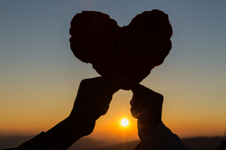 Heart in hands, loving couple and  sunrise background, Couple in love, Happy couple in love,  Love couple. Stock Photo