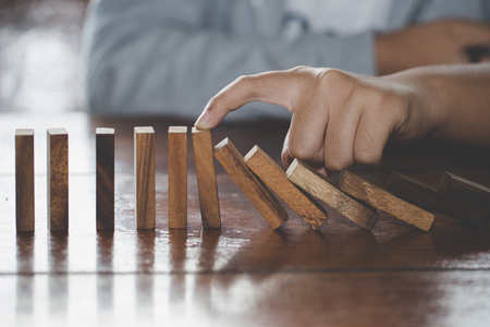 Businessman hand stopping falling wooden dominoes effect from continuous toppled or risk, strategy and successful intervention concept for business, game strategy, Invesment and Risk Management. Foto de archivo
