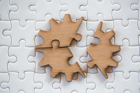 Three brown pieces of puzzle on a white jigsaw background, last piece of jigsaw puzzle to complete the mission, Business solutions, success and strategy concept Banque d'images