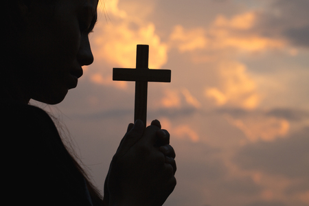 Silhouette of woman hand holding holy lift of christian cross with light sunset background.