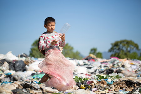 child walk to find junk for sale and recycle them in landfills, the lives and lifestyles of the poor, The concept poverty, child labor and human trafficking. Stock Photo - 116346552