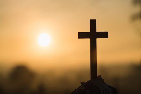 Gesù Cristo croce. Pasqua, concetto di resurrezione. Croce di legno cristiana su uno sfondo con illuminazione drammatica. Archivio Fotografico