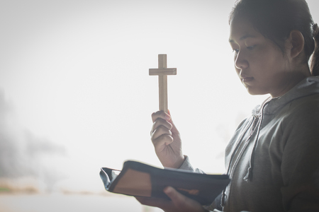 Young woman praying With the Holy Bible and the Holy Cross in the morning 版權商用圖片 - 117504988