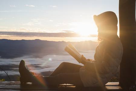Young woman praying With the Holy Bible  in the morning, Woman praying with hands together on the Sunrise background.