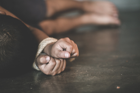 Victim boy with hands tied up with rope in emotional stress and pain,  kidnapped, abused, hostage,  Stop abusing violence, Children violence and abused concept Foto de archivo