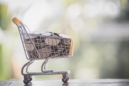 Carrito de supermercado con monedas, monedas en el carrito de compras, concepto de pago y ahorro de dinero, tienda de supermercado, finanzas y dinero