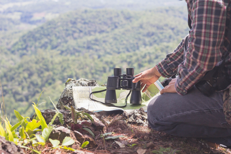 Young man with backpack and holding a binoculars sitting on top of mountain, Hiking and tourism concepts