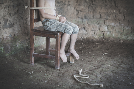 The boy was tied at the corner of the abandoned house, Stop violence against children and trafficking. 版權商用圖片 - 117526700