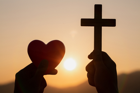 Silhouette of woman hands praying with cross and holding a red heart ball in nature sunrise background, Crucifix, Symbol of Faith. Christian life crisis prayer to god, The concept of loving God.