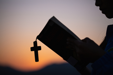 Women hand  pray to God with the Bible and the cross of the morning. Woman Pray for god blessing to wishing have a better life. Christian life crisis prayer to god.