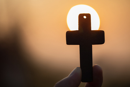 Woman hand holding holy lift of christian cross with light sunset background.