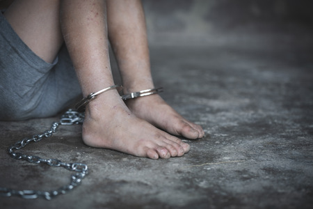 Hopeless childs foot locked with handcuffs, human trafficking, Violence against children. Stock Photo