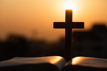 Silhouette of the wooden cross over opened bible with a bright sunrise as background , Christian, god.
