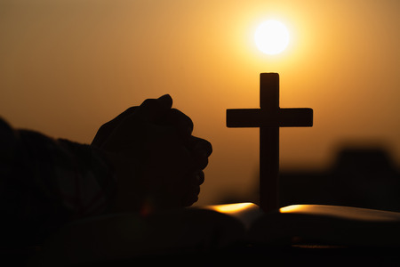 Silhouette of young woman praying with crosses and bibles at sunrise, Christian Religion concept background.