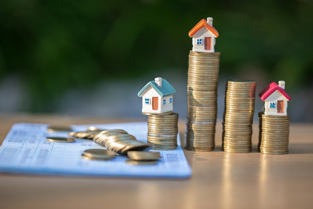 Coins and financial statement or saving account book on  table, Business, finance, saving money, property ladder or mortgage loan concept,  house model.