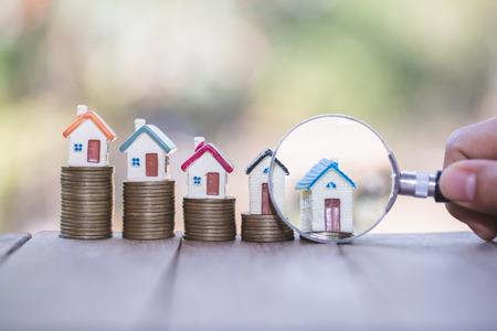 Concepto de búsqueda de casa con lupa, casa y dinero. lupa y monedas. concepto de hipoteca, construcción, alquiler de vivienda.