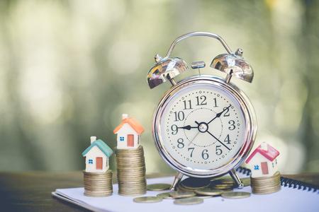 pila de monedas de dinero que crecen con el modelo de la casa y el concepto de reloj despertador en los negocios sobre la venta de préstamos, hipotecas de financiamiento y compra de casa, tono Vintage. Foto de archivo
