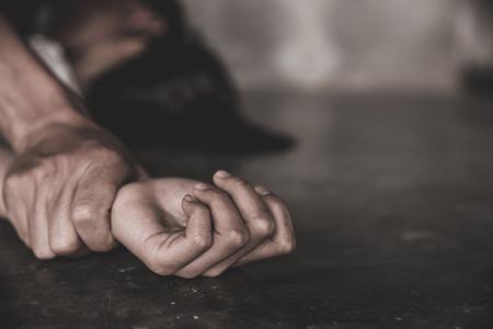 Mano dell'uomo che tiene la mano di una donna per stupro e abuso, concetto di mani per stupro e abuso, abuso sessuale è un problema o concetto di questioni sociali.