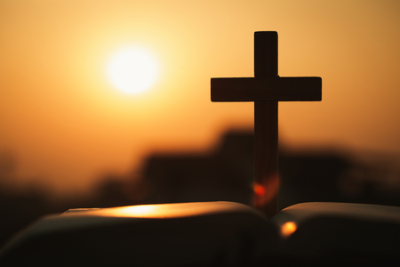 Silhouette of cross and bible with the sunset as background, christian concept, spirituality and religion