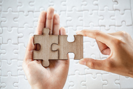 Closeup hand of man connecting jigsaw puzzle with sunlight effect, Business solutions, success and strategy concept Stockfoto